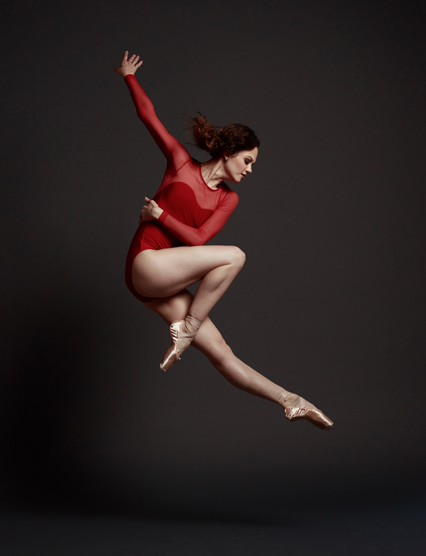 Ballerina wearing red jumping in studio