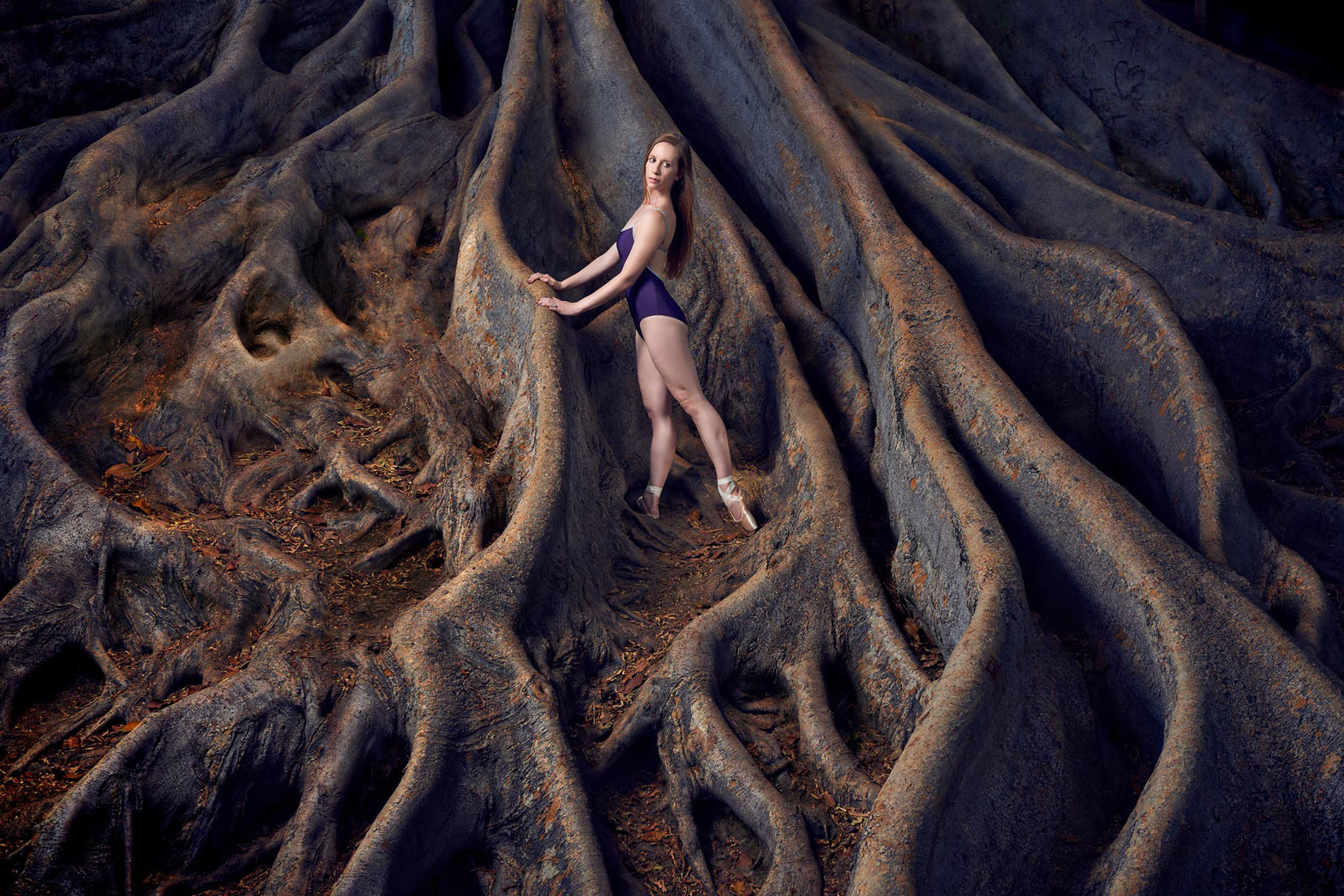 City Ballet of San Diego ballerina posing by tree in Balboa park.