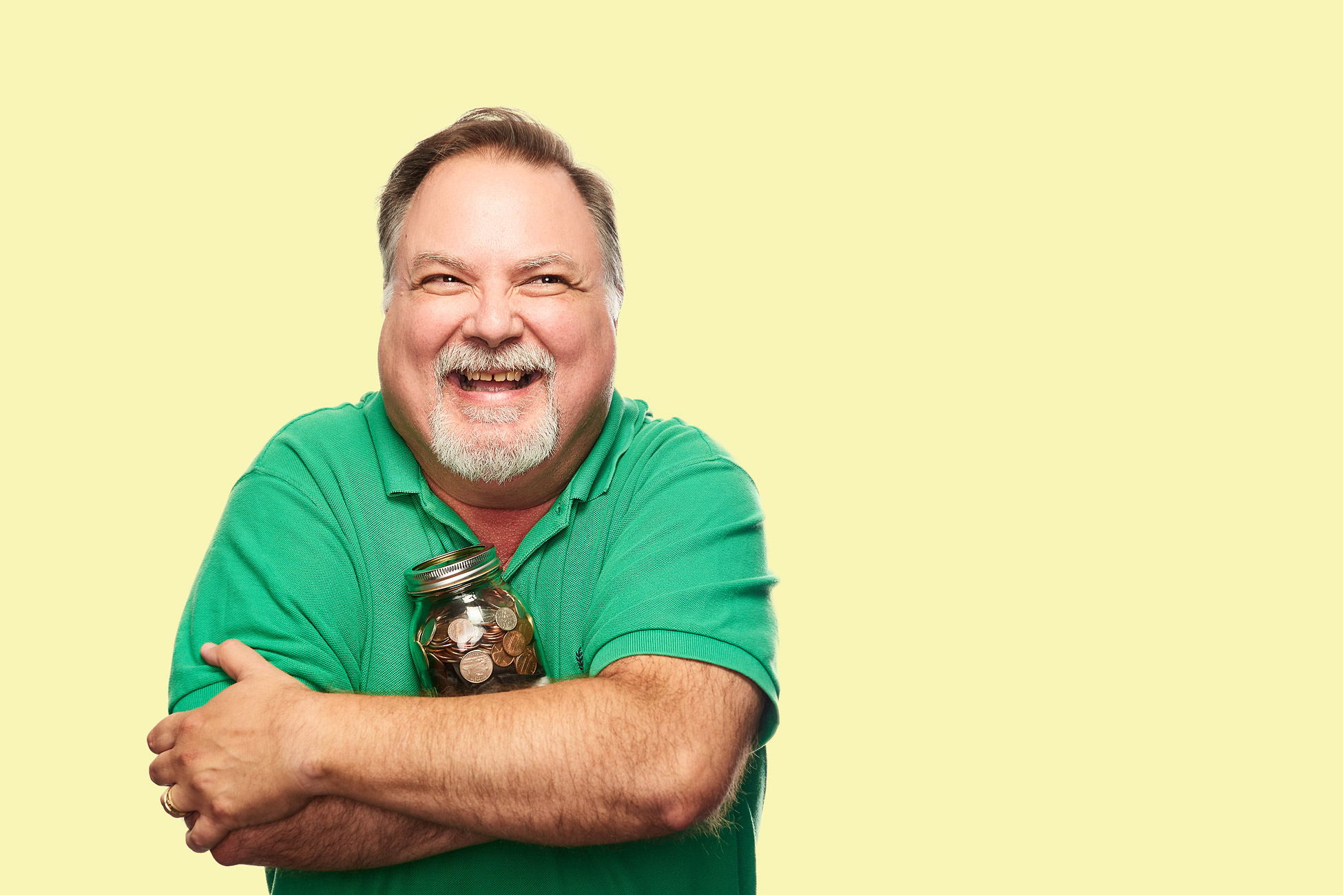 Man in green shirt  holding piggy bank on yellow background.