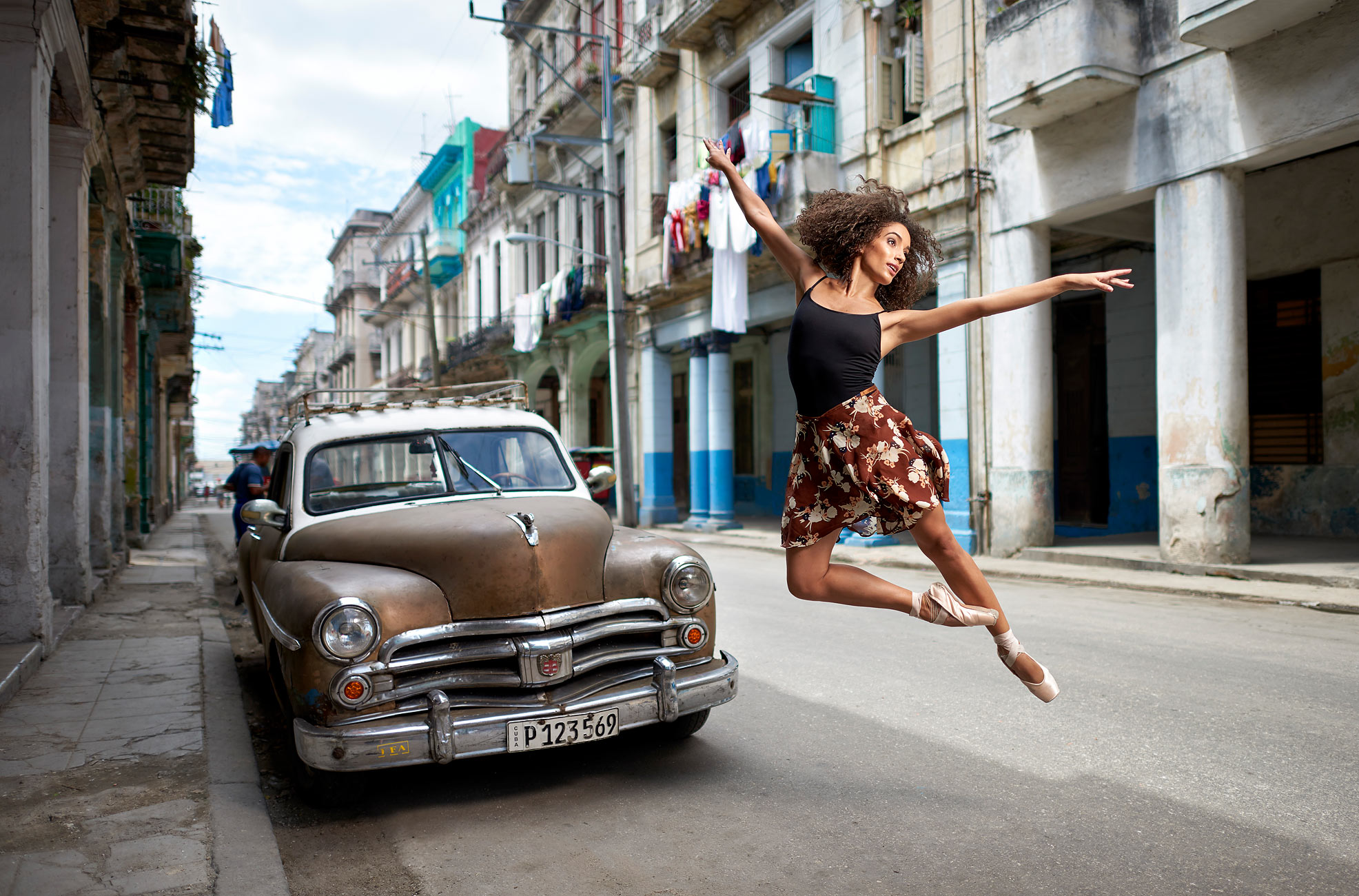 Cuban Ballerina Brenda Estrada jumping next to old car.