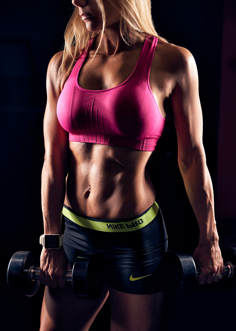 Fitness Model holding dumbbells on black background.
