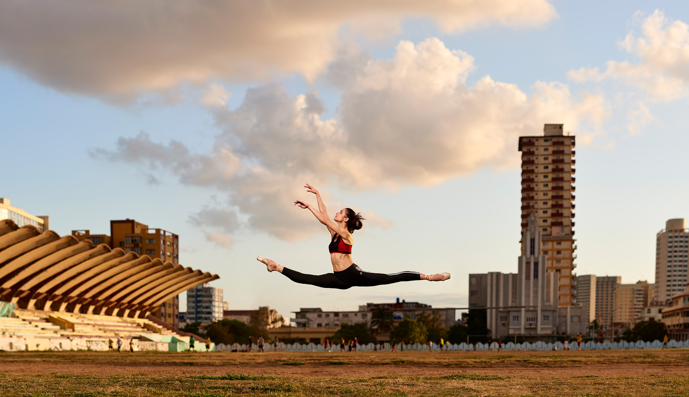 Gabriella jumping with Jose Marti Stadium, Cuba in background.