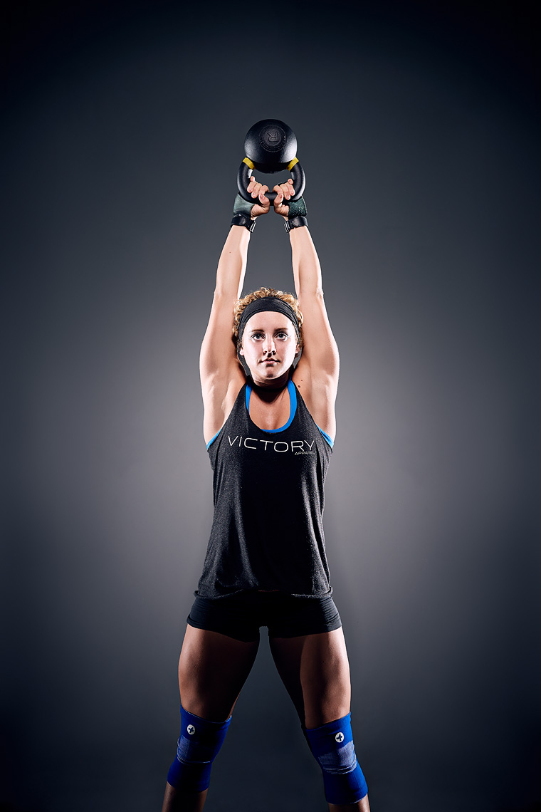 Woman swinging kettlebell overhead.