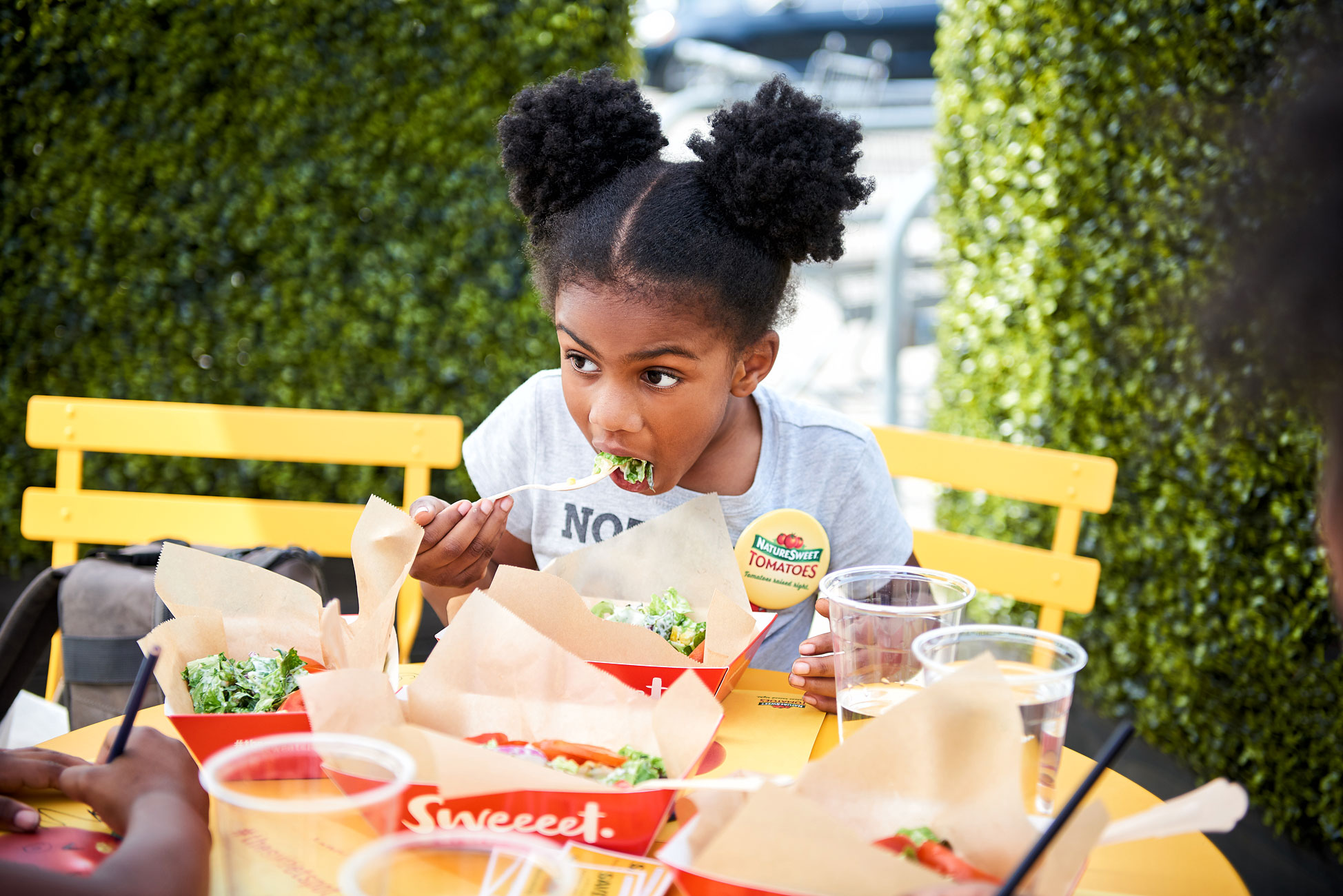 Girl with pigtails eating salad at outside yellow table.