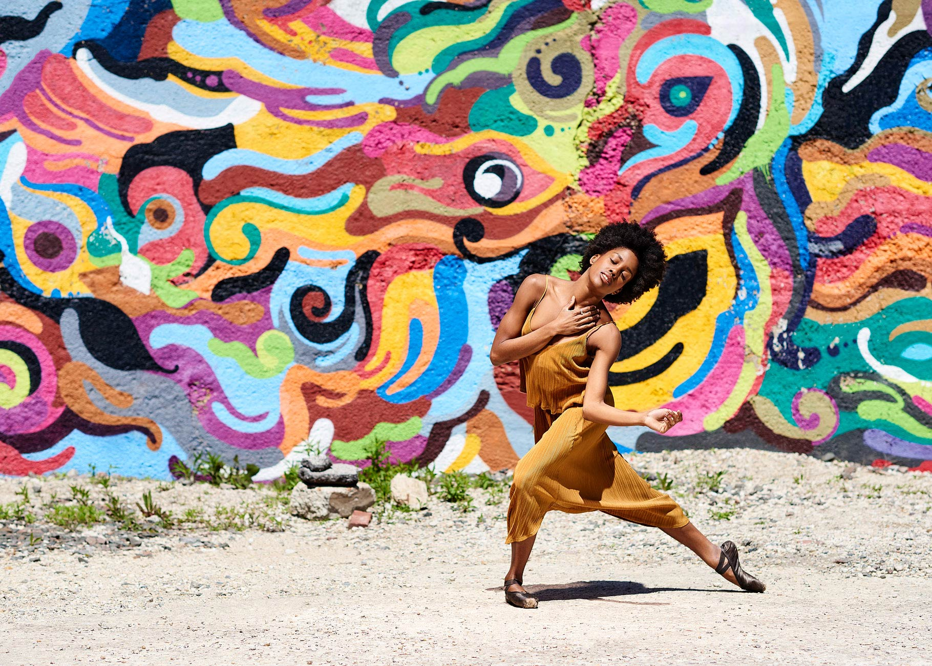 African American ballet dancer posing with colorful wall behind her.