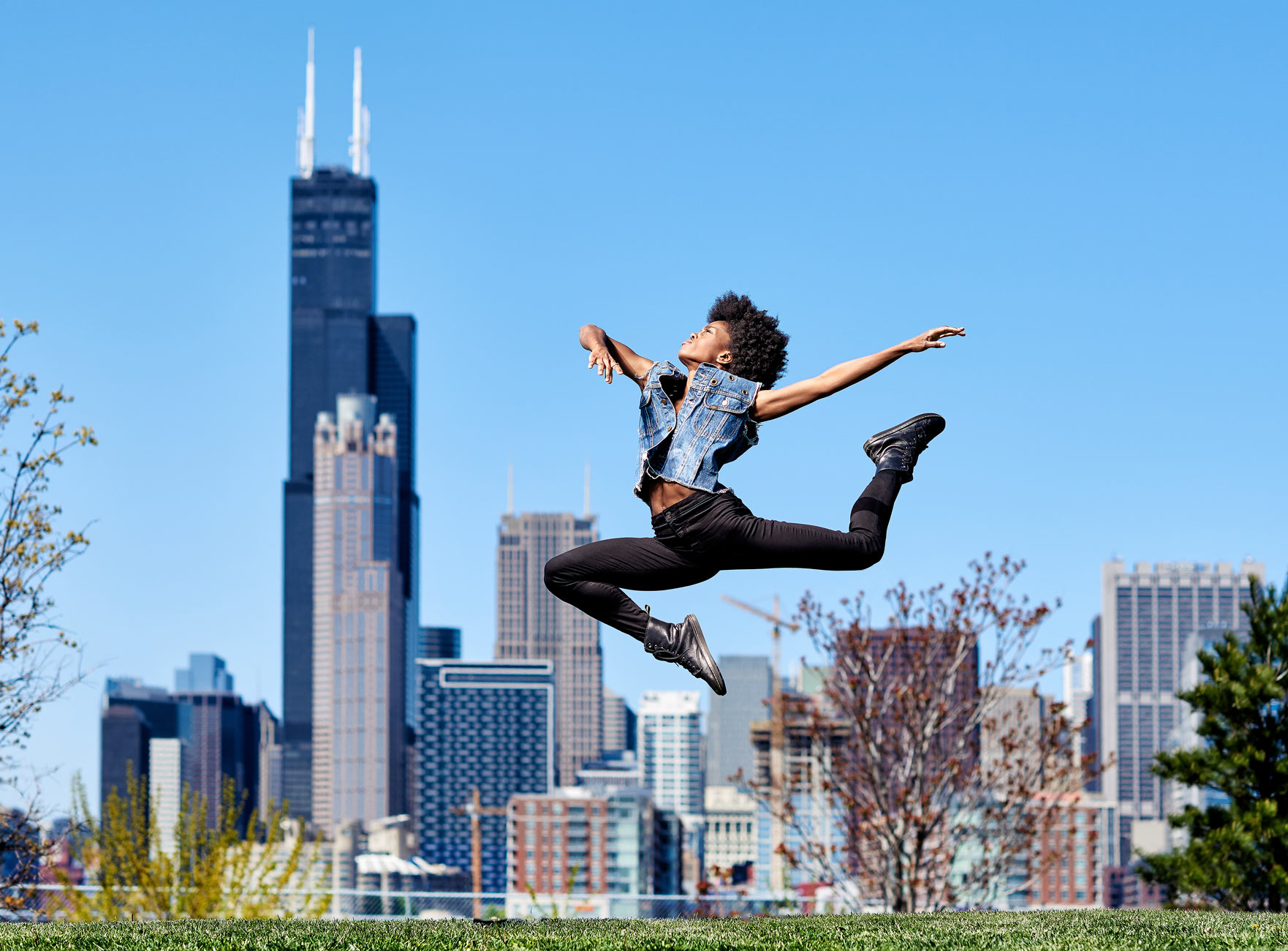 Dancer jumping with the Sears tower in background in Chicago.