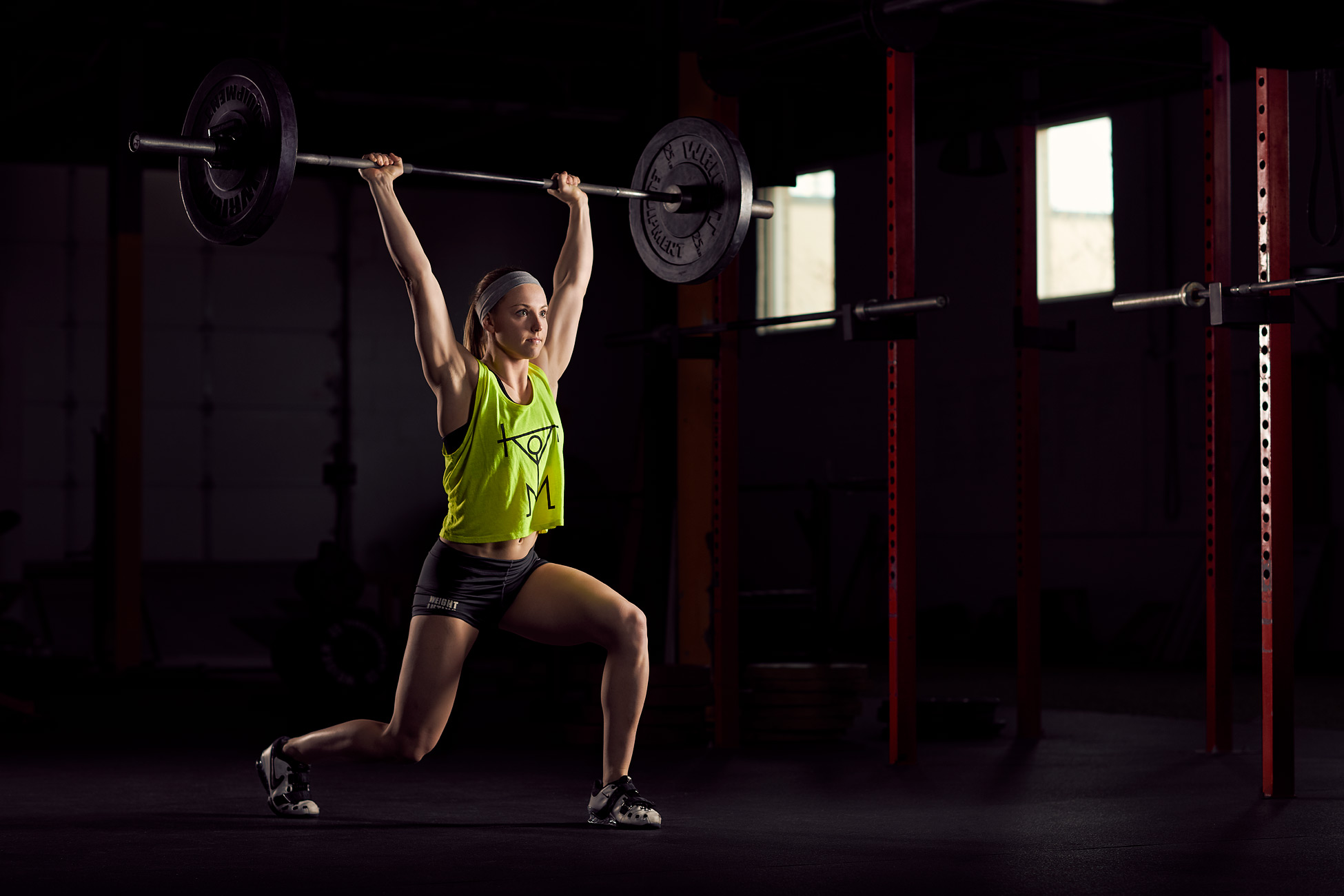 Woman Olympic Weight Lifter in dark gym in St. Louis, Missouri.