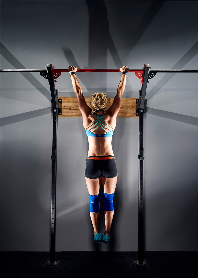 Woman performing pullup in gym.