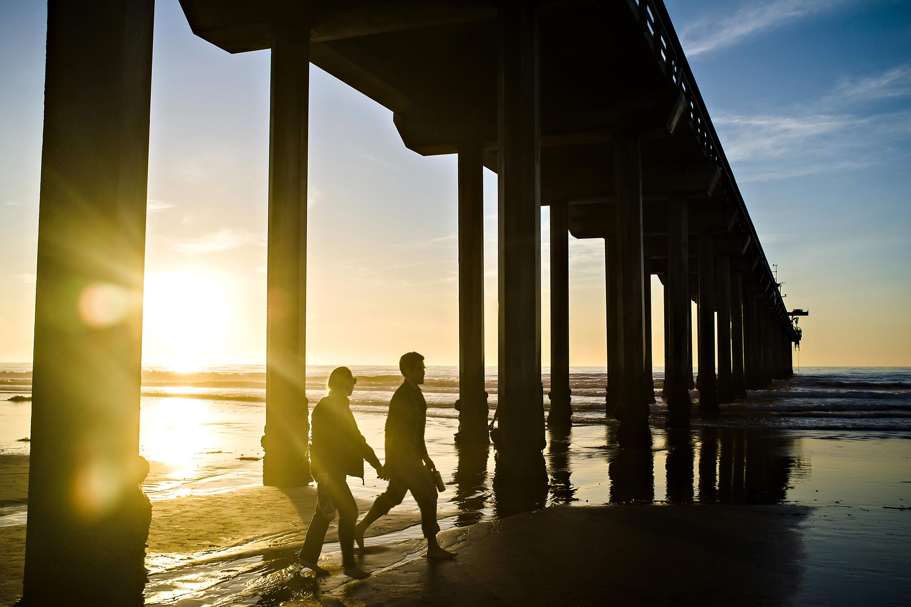San Diego Scripps Pier at sunset with couple walking.