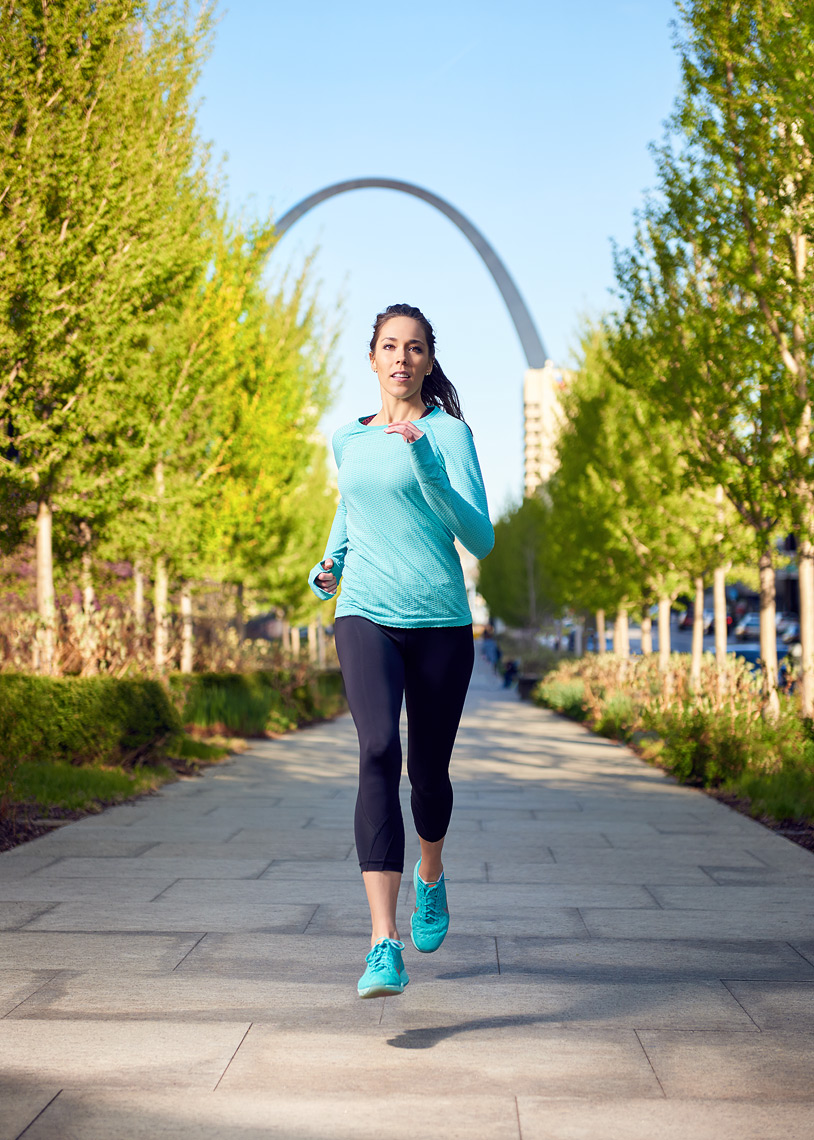 Woman running with St. Louis Arch in background.