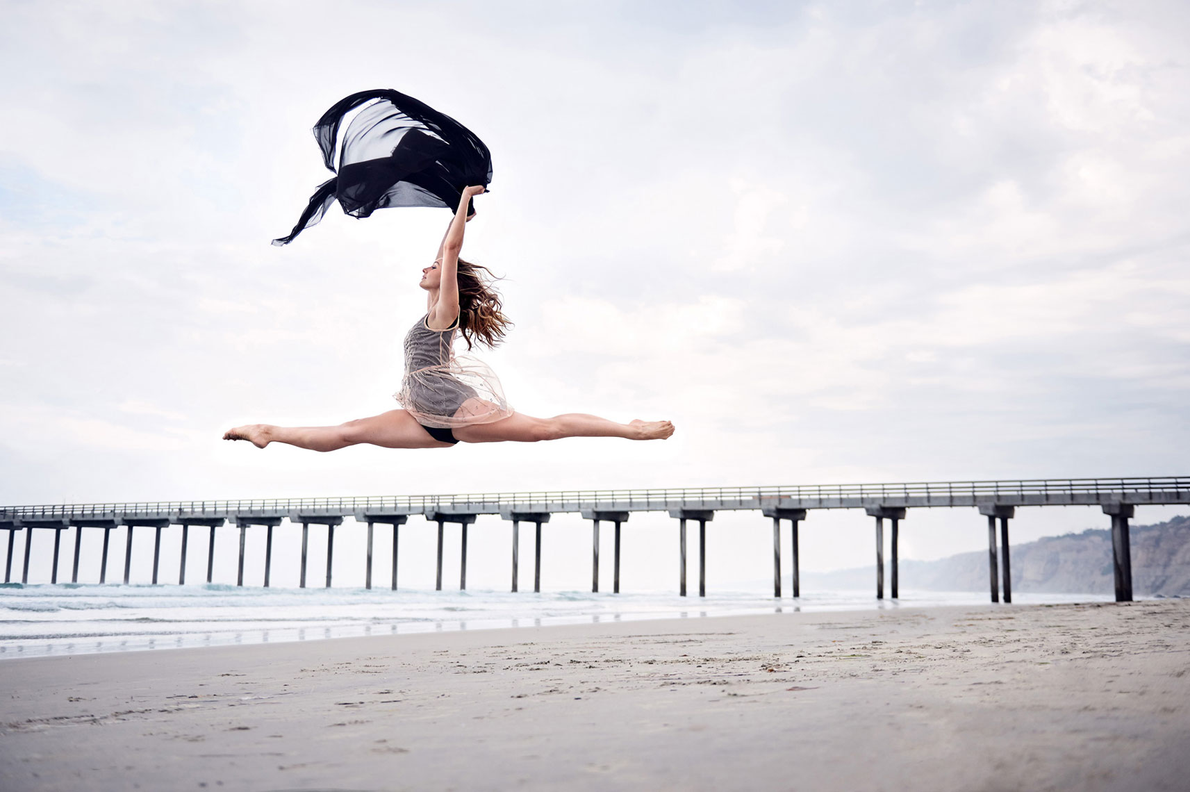 Ballerina jumping with Scripps pier in background.