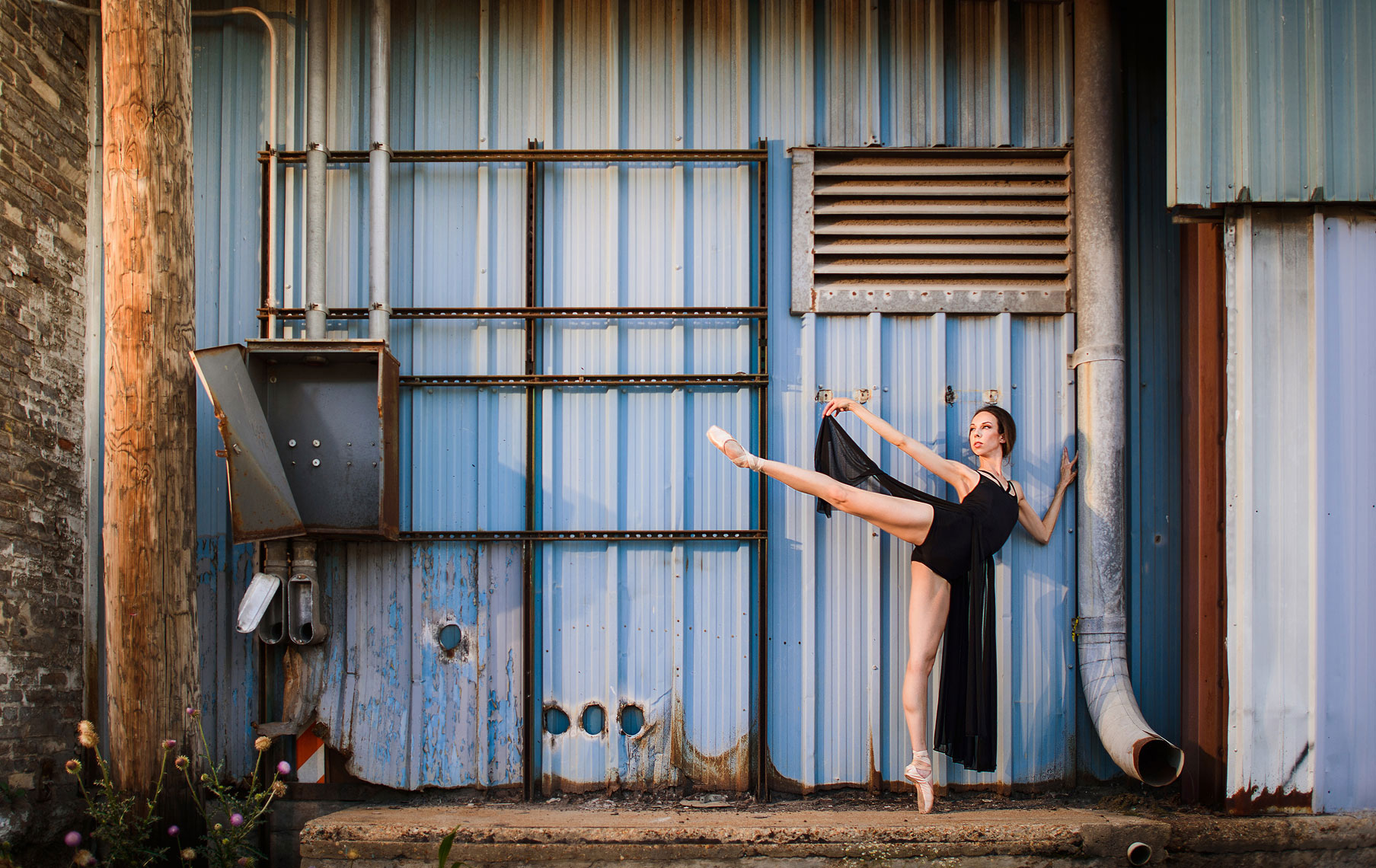 Ballet dancer posing on exterior of abandoned building.