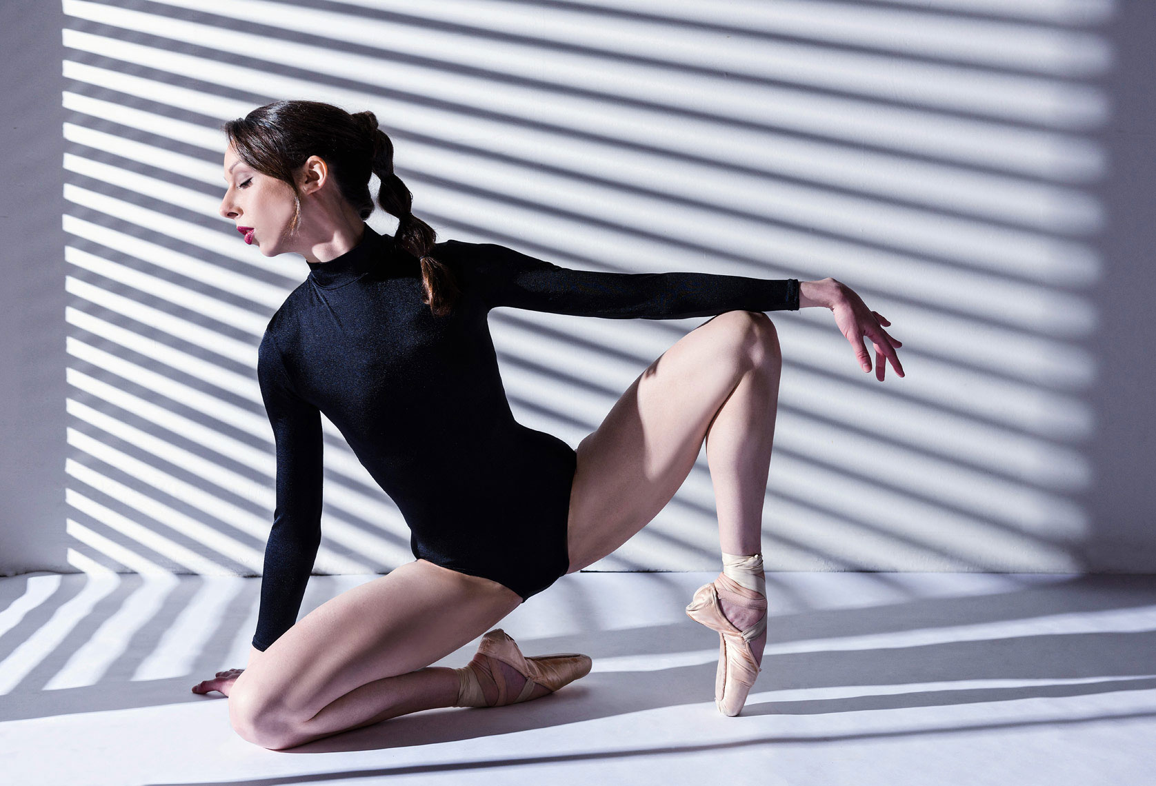 Ballerina posing in studio with lines on background.